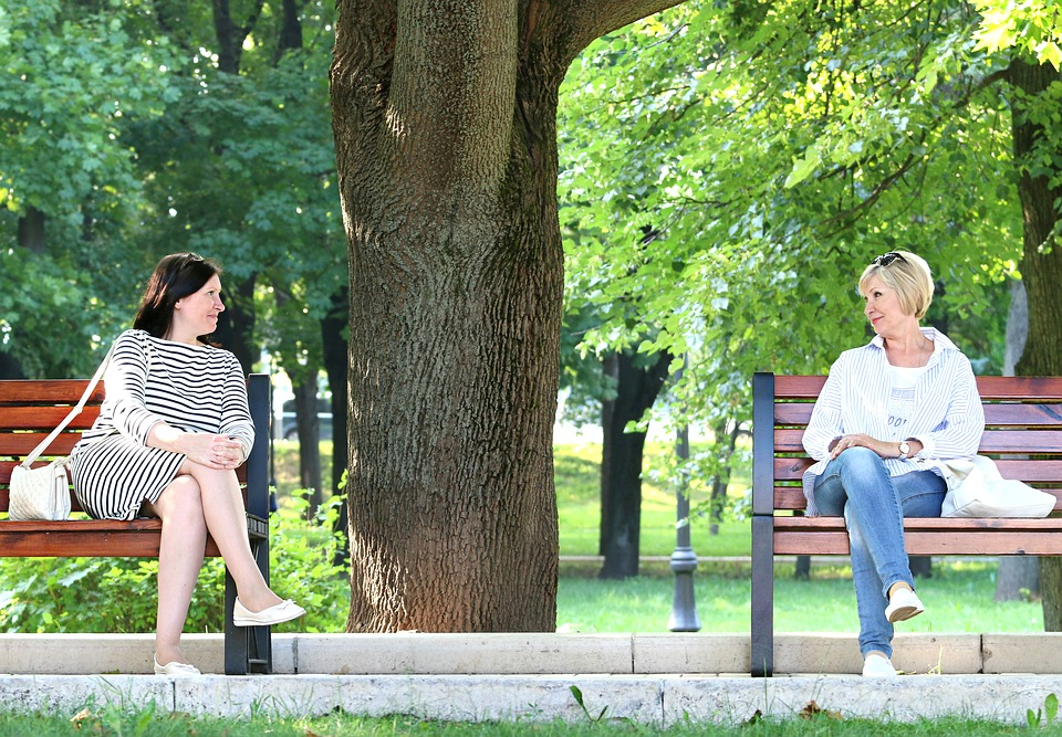 A conversation. In a park. Between two women. Sitting on benches.